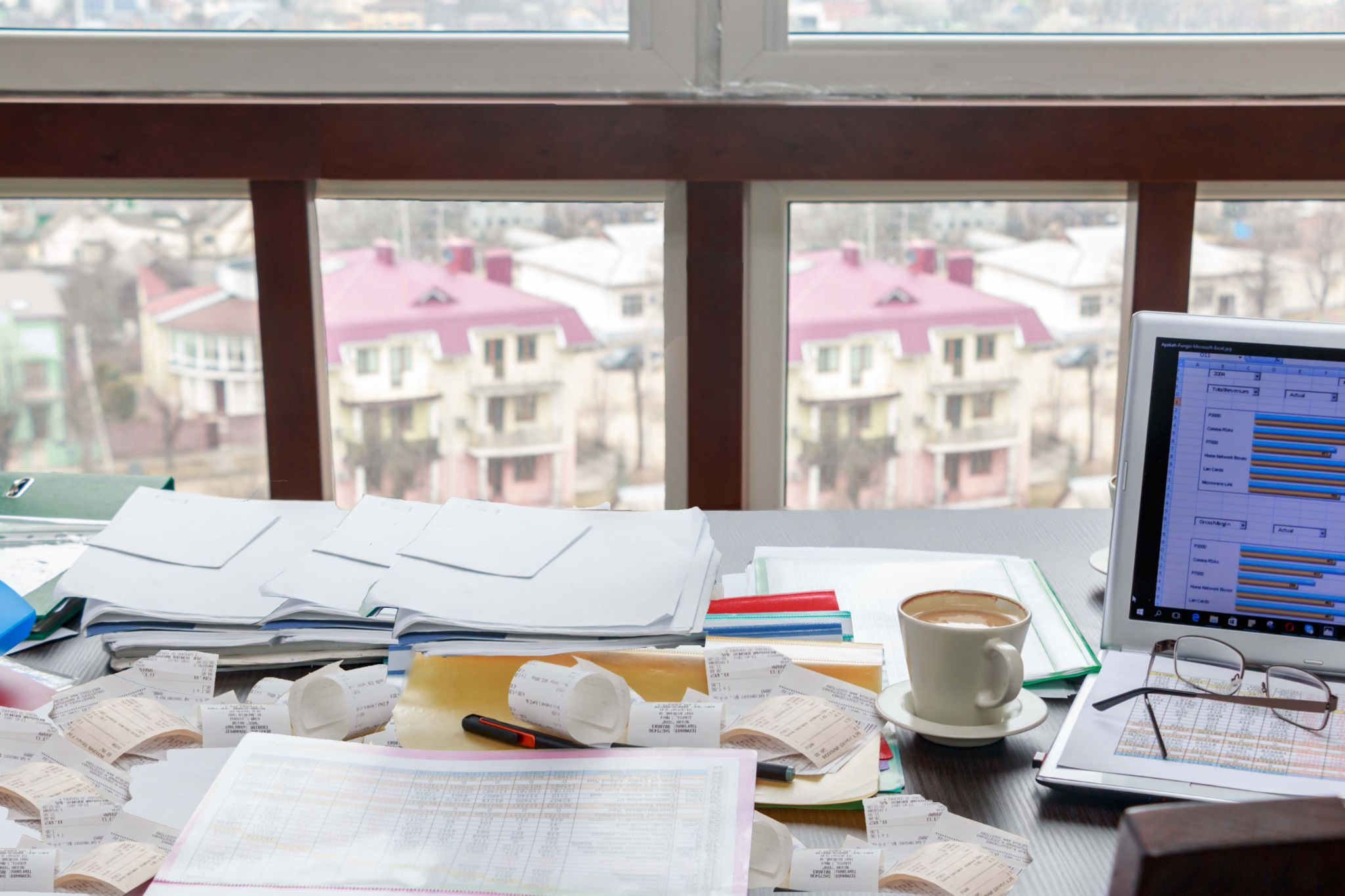 Messy desk covered in papers and receipts.
