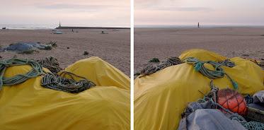 Duas imagens separadas por uma pequena barra branca. Nas duas, em primeiro plano, um oleado cobrindo instrumentos de pesca e algumas cordas sobre ele. Ao longe, na da esquerda o quebra-mar e um barco de pesca, na da direita o areal imenso, vazio. Céu de entardecer, ligeiramente alaranjado