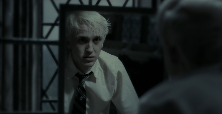 Still from Harry Potter and the Deathly Hallows, Part 2. Draco Malfoy, in his school uniform, looks at his reflection in a bathroom mirror. He is pale against the dark background, and looks fearfully into his own eyes.