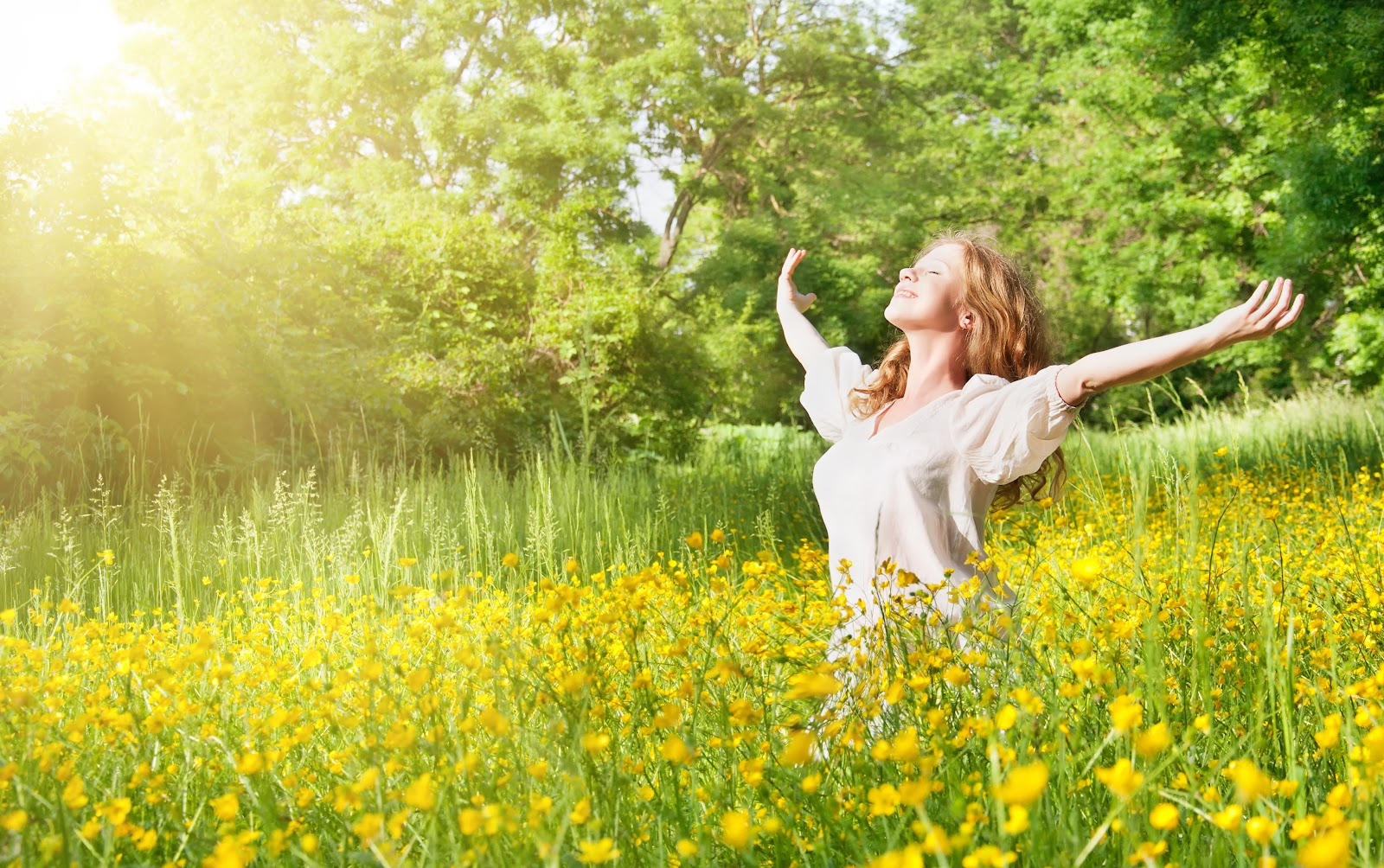 A woman in a field feeling contentment and happiness