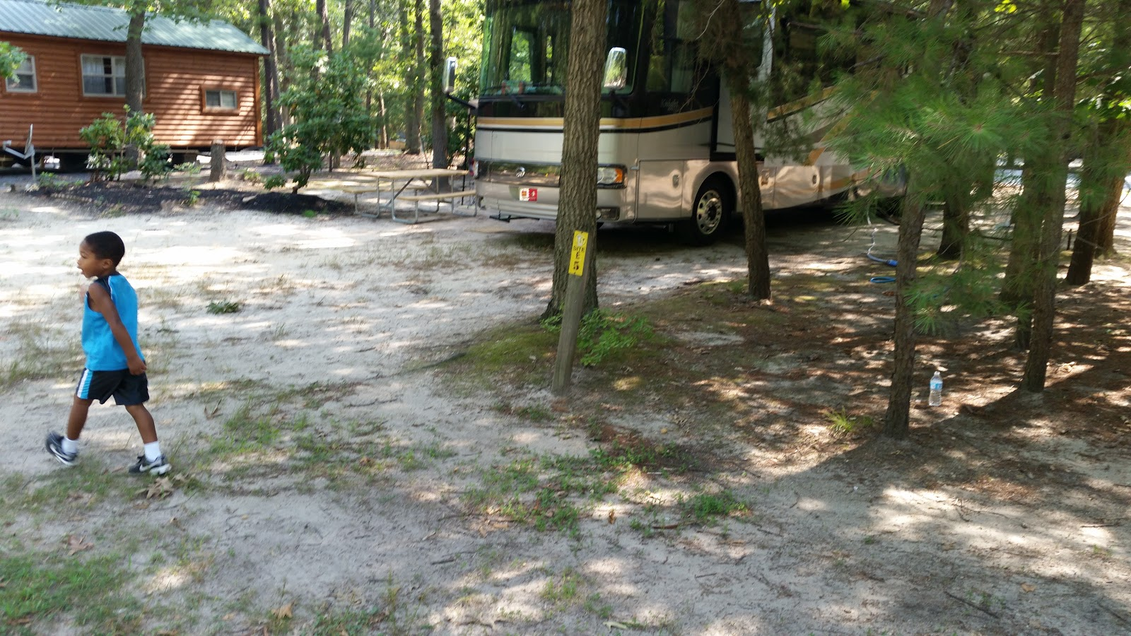 Young boy walks in campground by Class A motorhome