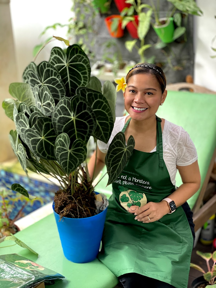 A person smiling next to a potted plant  Description automatically generated with low confidence