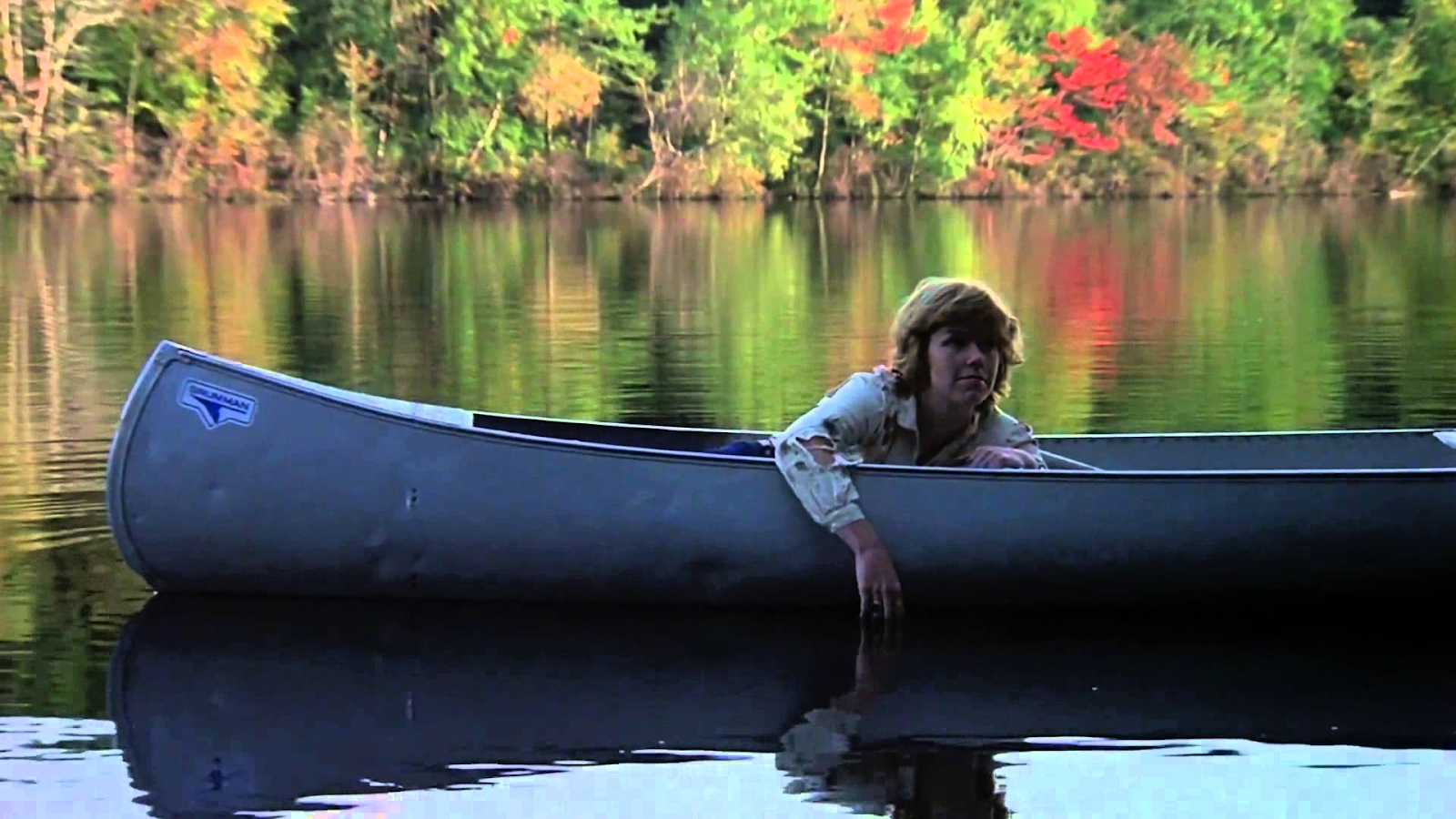 Still from Friday the 13th (1980). A young woman, Alice, lays in a canoe on a still lake. Her shirt is torn and dirty, and she reaches an arm over the edge to trail her fingers in the water.