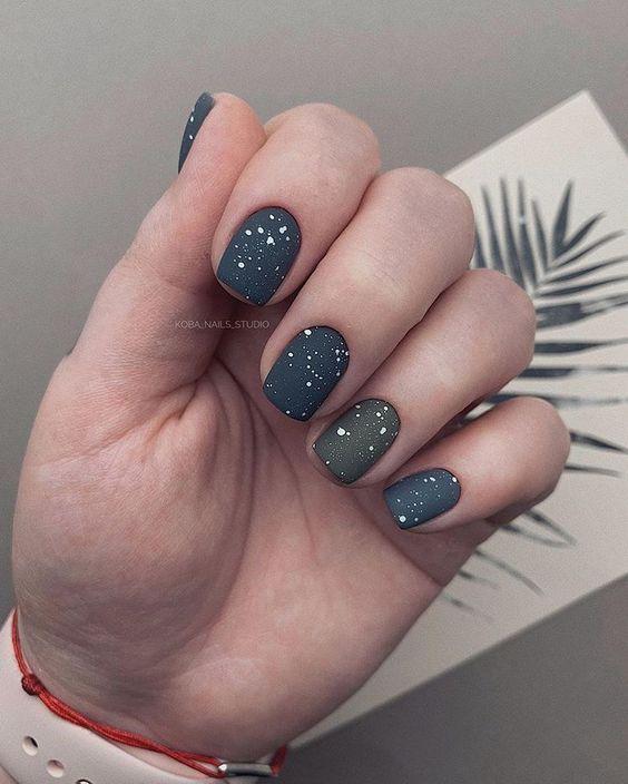 Mão com unhas pintadas de cinzas e pingos brancos. Foto: Pinterest/ Koba_Nails_Studio. Post: Nail art fáceis para fazer em casa