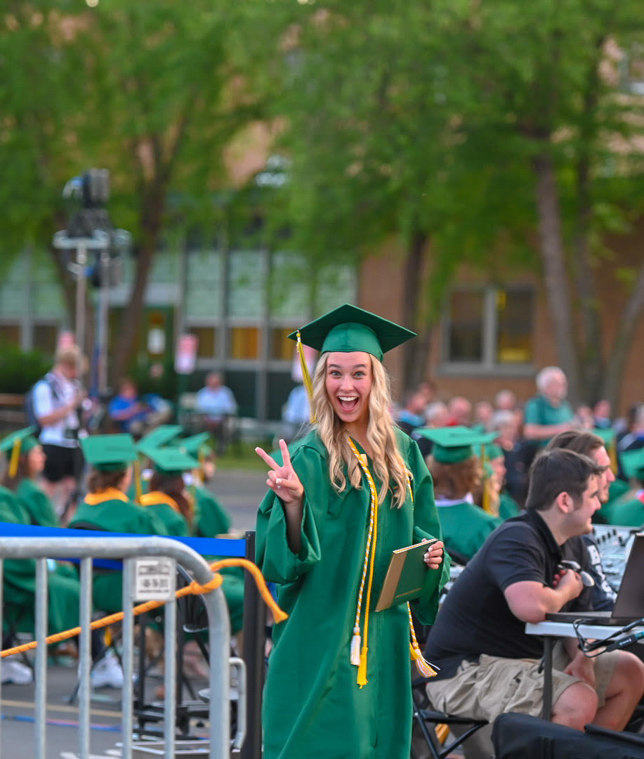Photo of a blonde haired teen wearing a green cap and gown giving a peace sign
