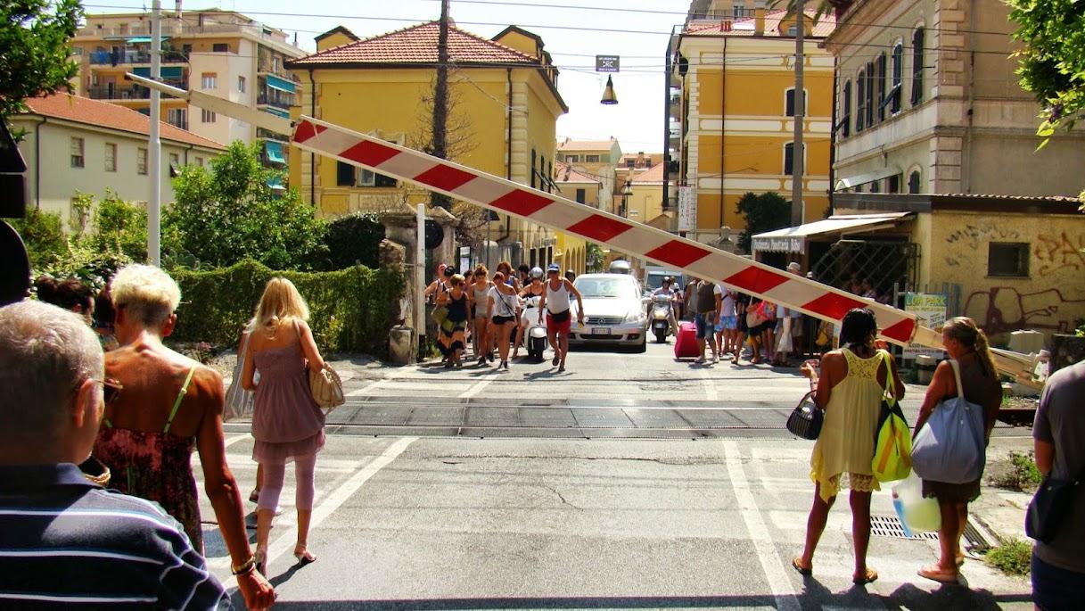La gente se apura para cruzar la barrera. Si enlaza dos trenes, no podrás cruzar en 20 minutos