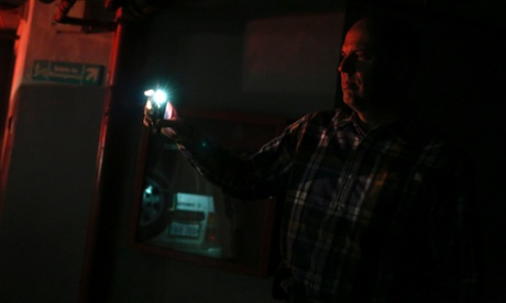 A man uses light from his phone to find his car during a blackout in Caracas.