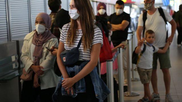 Пассажиры рейсов из Калифорнии и Турции ждут на паспортном контроле в Берлине, 29 июля, 2020 год