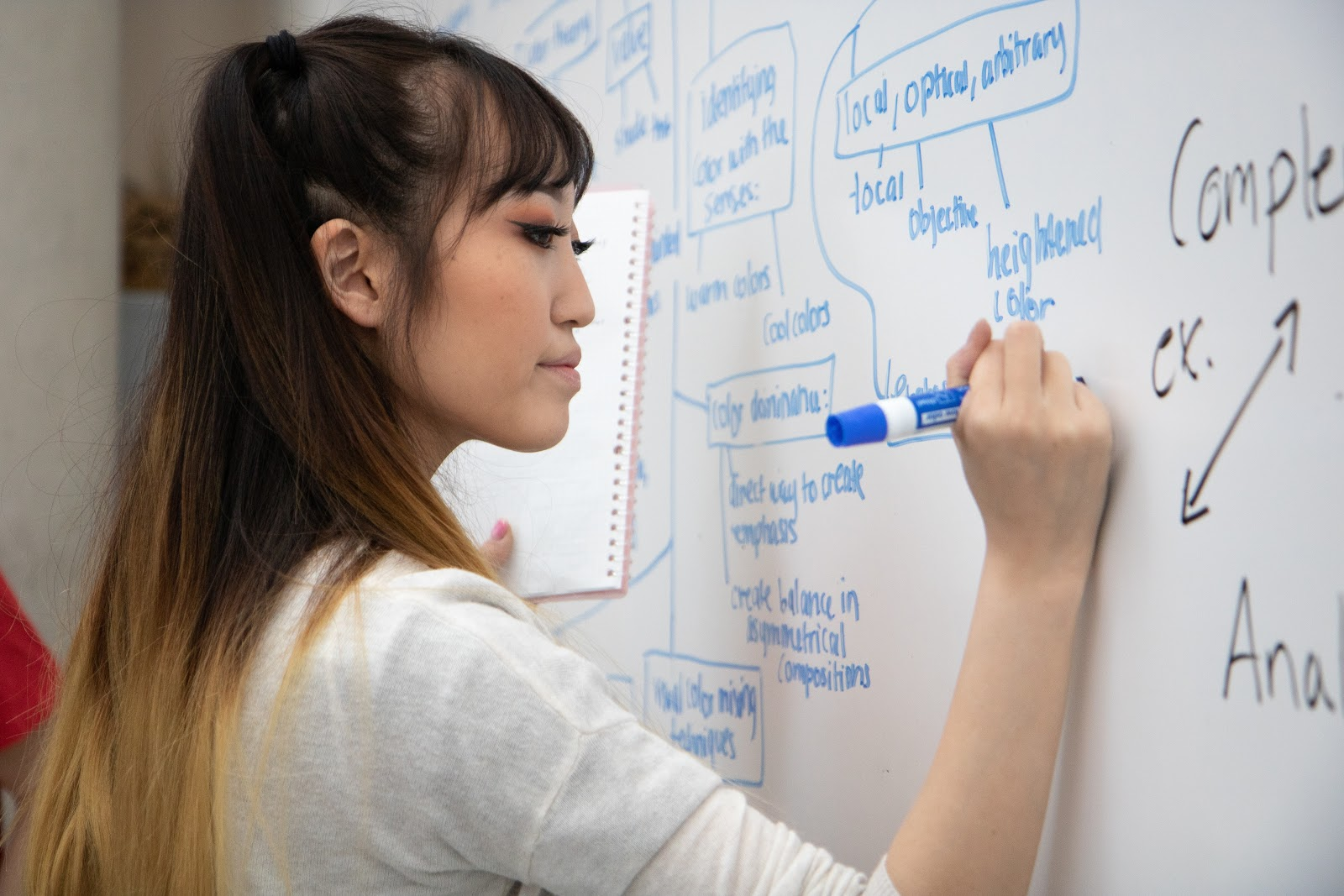 A student writes on the whiteboard in her <mark><mark><mark>classroom</mark></mark></mark> with a blue sharpie marker in her right hand and a notebook in her left.