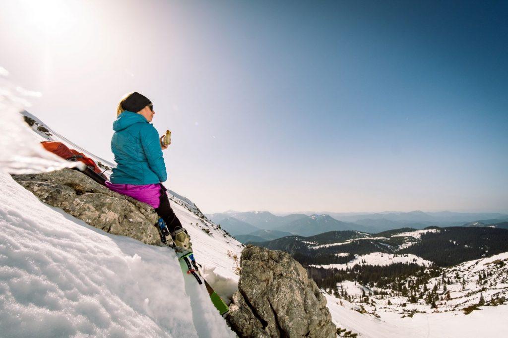 Esquiadora tomando un sandwich con vistas las montañas