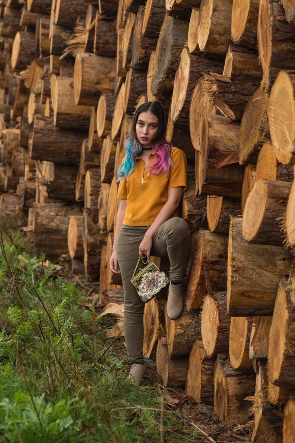Mulher posando ao lado de um monte de troncos de árvore.