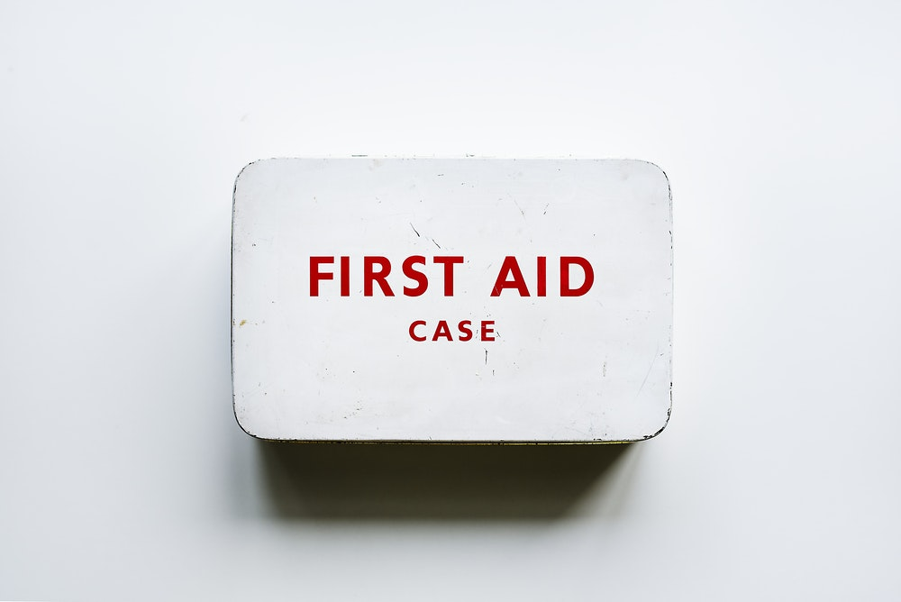 white and red first aid case on wall