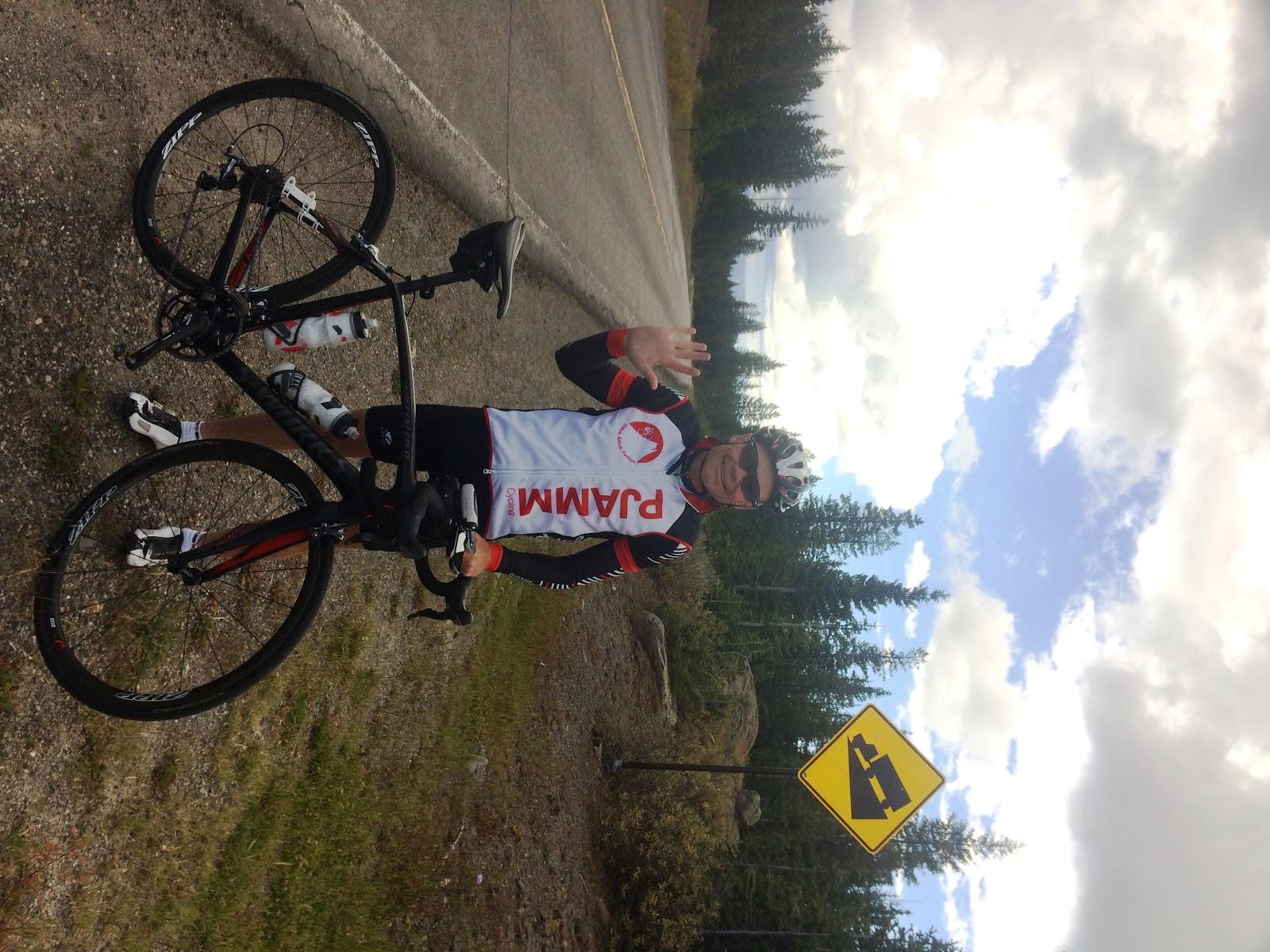 Biking to Grand Mesa North - cyclist with bike and steep grade sign