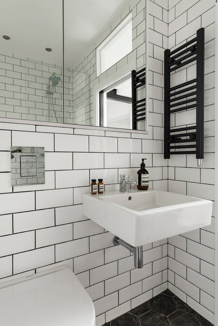 Bathroom with white metro tiles, black grouting and a black heater.
