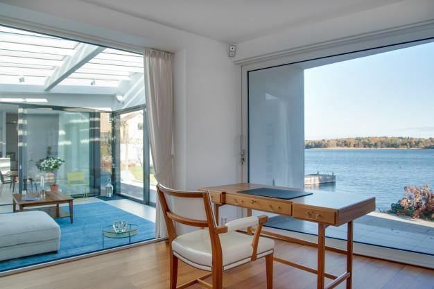 Casa de praia luxuosa com janelas de vidro e a bela paisagem do mar Foto gratuita