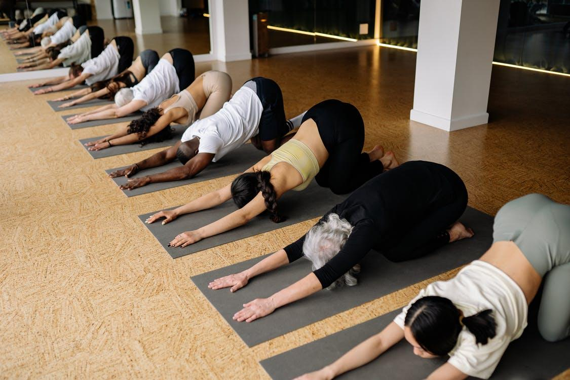 People Doing Stretching in Yoga Class