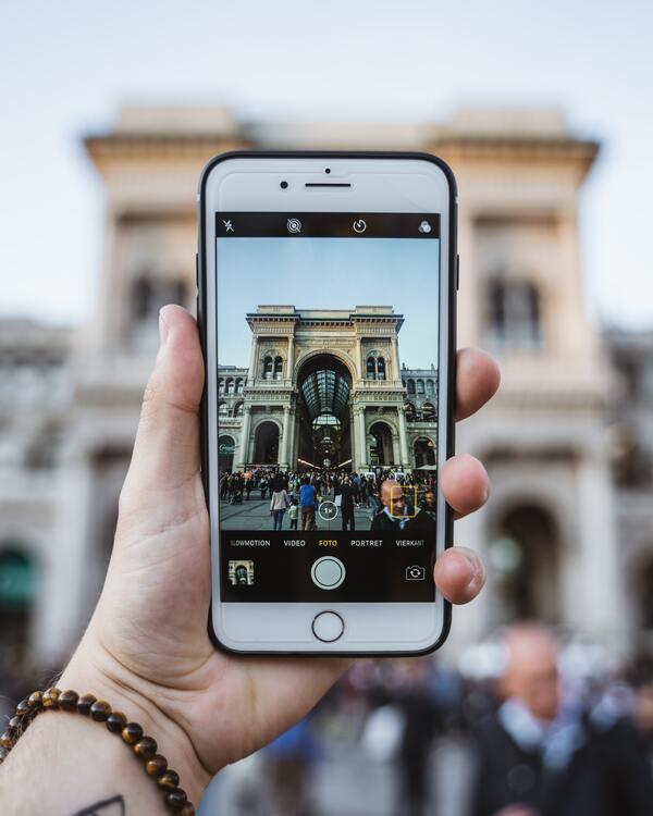 Foto de uma mão segurando o celular e tirando foto de uma arquitetura.