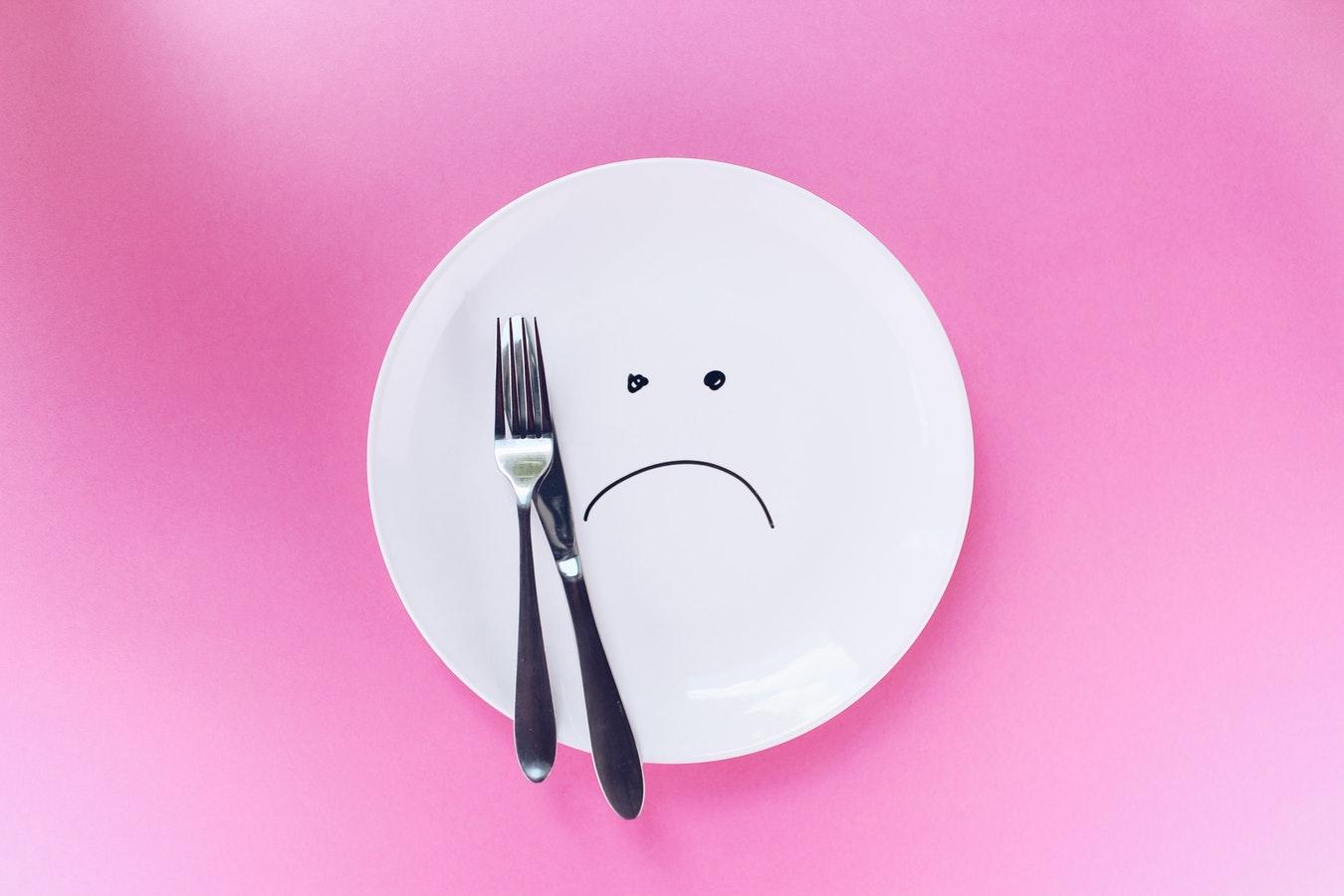粉紅色背景中,有一個白色的盤子,上面畫了一個哭臉。