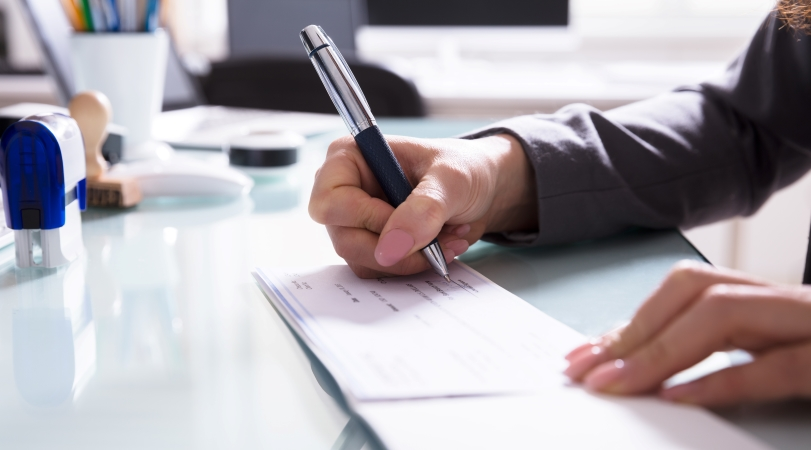 a man signs a lump sum check for a new employee's relocation package
