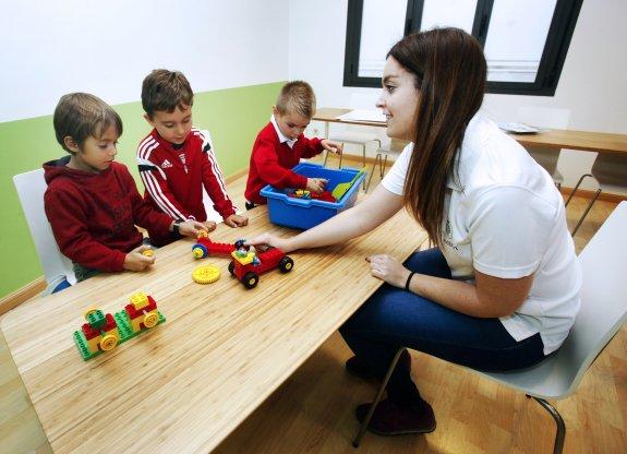 Tres jóvenes alumnos reciben clases por parte de una de las profesoras de 'TIC and BOT'. ::