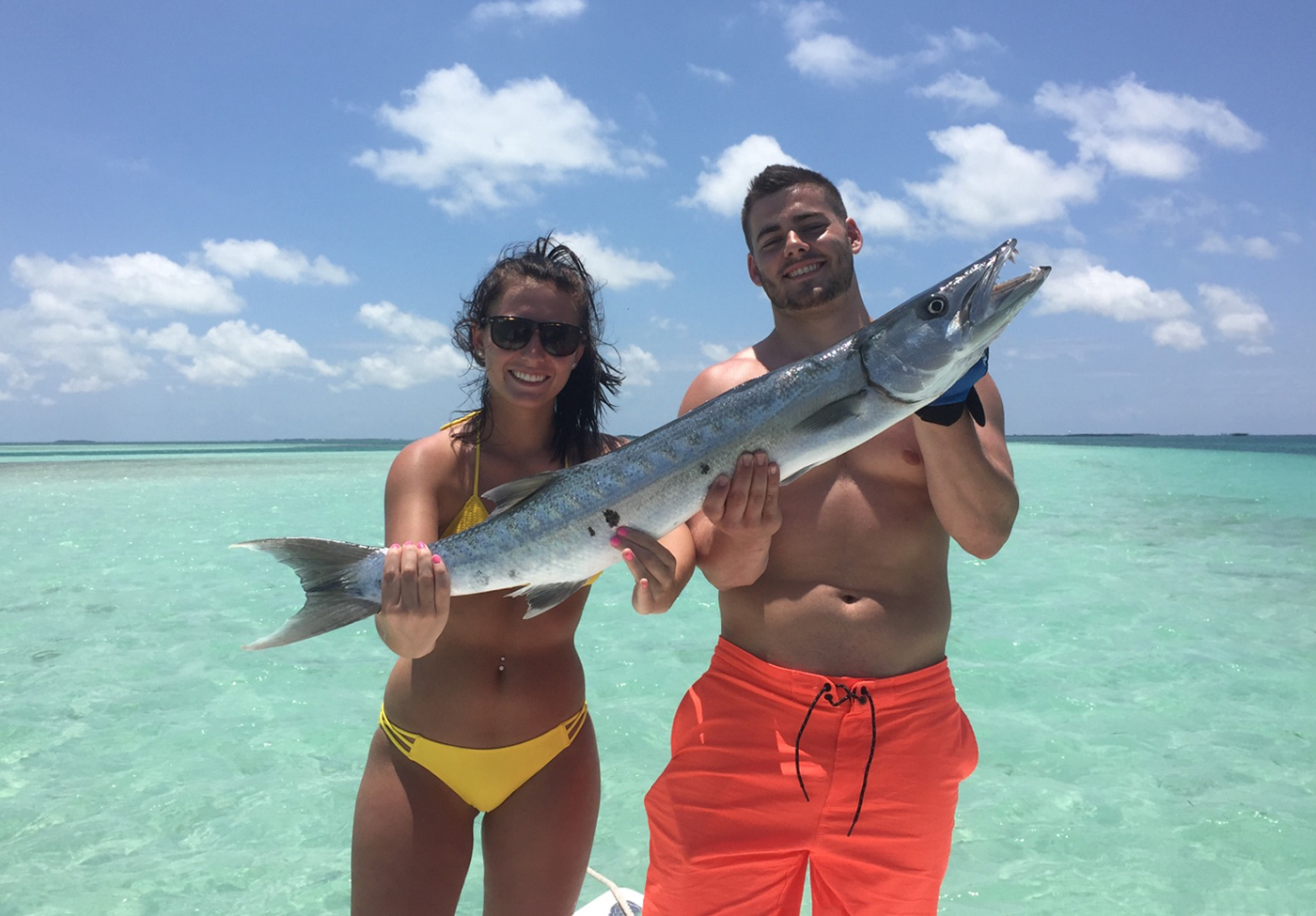 A man and woman holding a Barracuda in the shallow waters of Key West