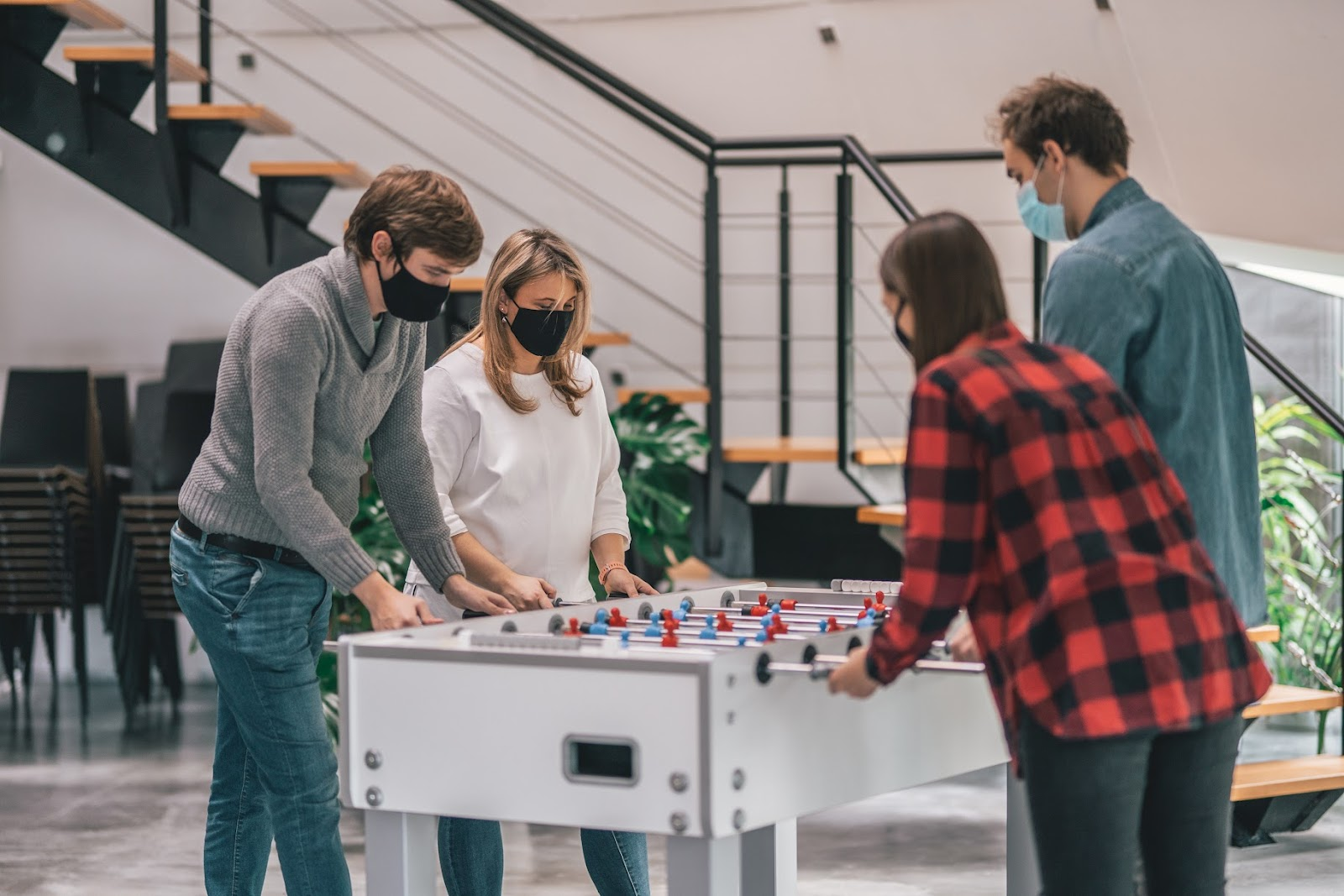Office workers playing table football
