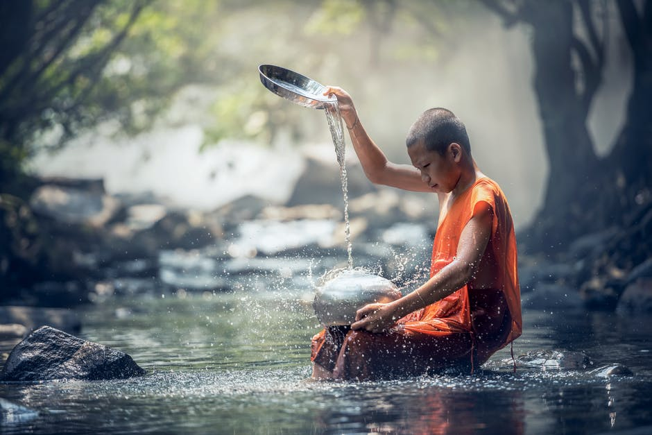 Monk Washing Dishes on River