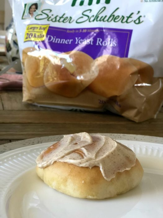 A bag of Sister Schubert\'s rolls with a roll sitting on a plate with butter.