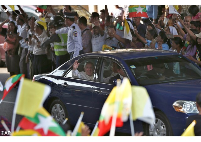 Pope Francis is greeted by cheering, flag waving crowds as he arrives in Yangon's city centre - AP