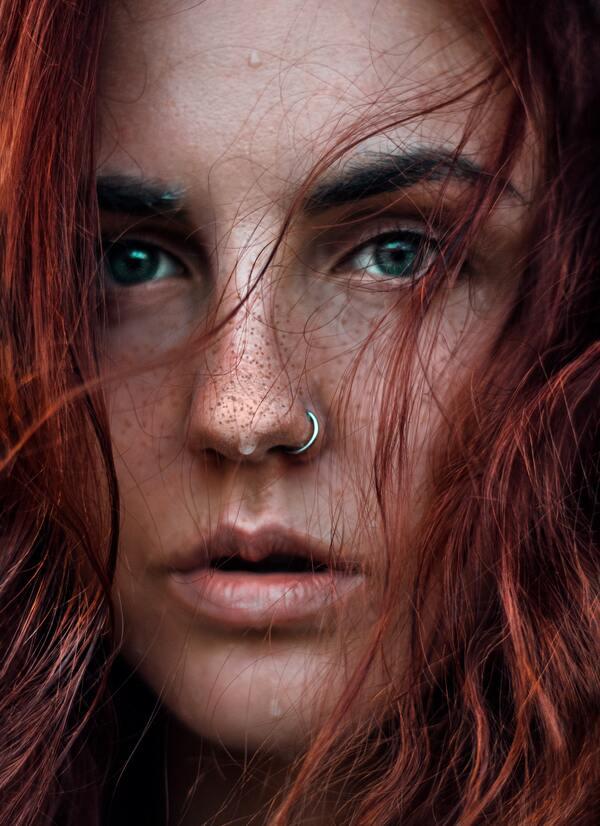 Foto do rosto de uma mulher ruiva com sardas
