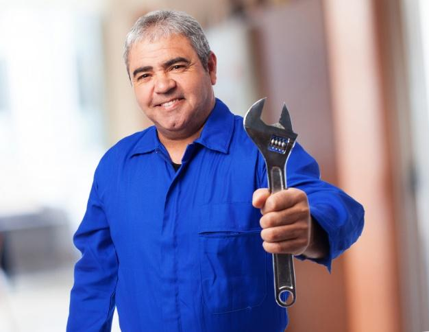 Homem sênior com macacão azul que prende uma chave Foto gratuita