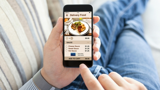 Pictured: a person holding a smartphone with a food planning app open on it.