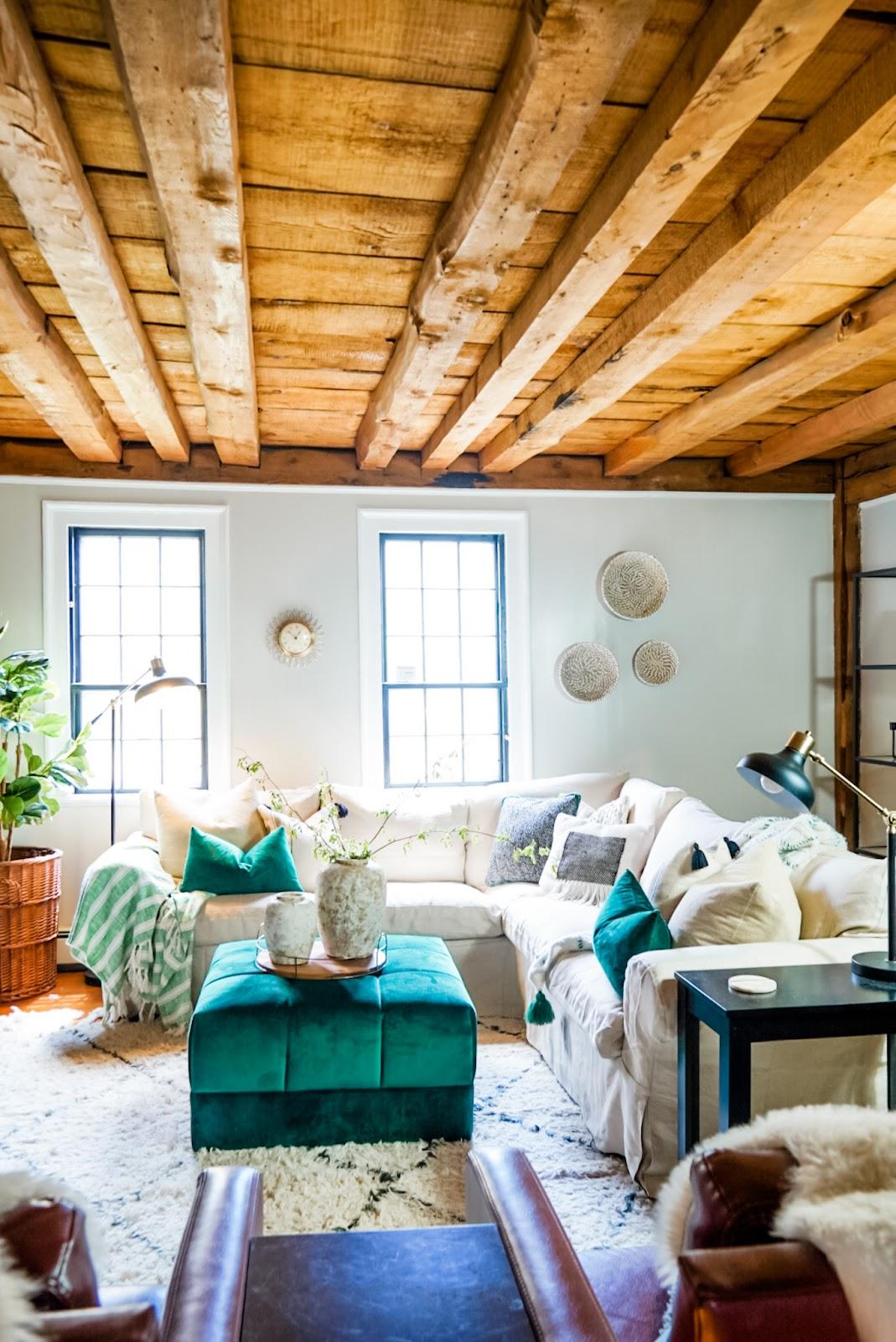 Living room with a sectional slipcover couch and emerald green accents.
