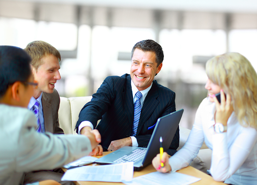 Businessman shaking hands with another business man during a meeting with several team members.