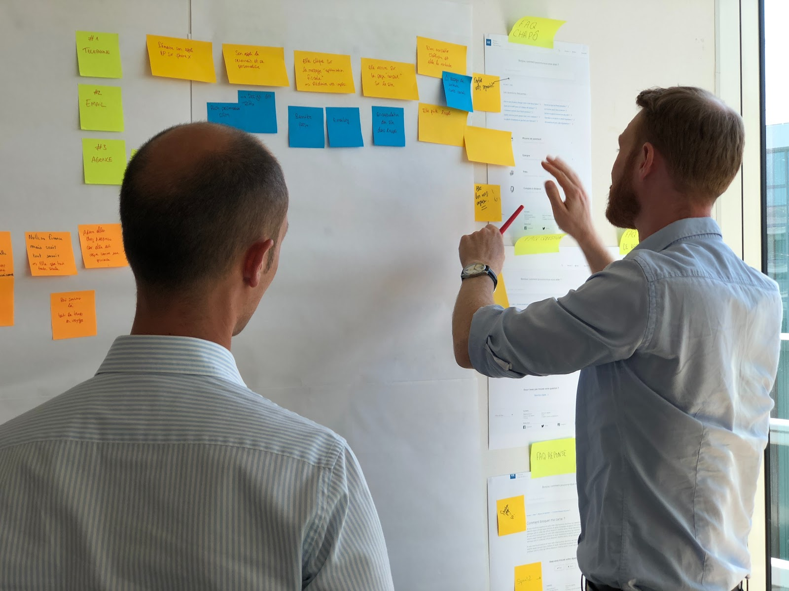 Two men discussing sticky notes on a board.