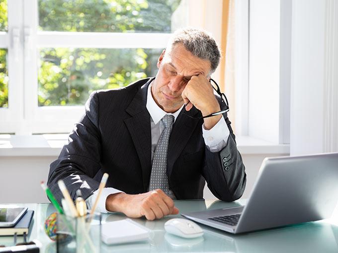 Mann sitzt mit geschlossenen Augen am Schreibtisch und stützt seinen Kopf auf - die Blutzuckerschwankungen bei Diabetes haben oft Müdigkeit zur Folge.
