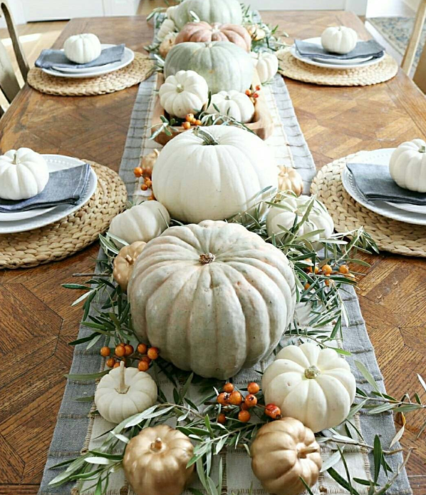 How to use pumpkins to decorate. Image shows beautiful wood table set for dinner for 4 place settings. A blue and white table runner with a mixture of white and gold and green pumpkins with leaves and orange berries for decoration.