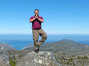 Mann balanciert einbeinig auf Bergspitze