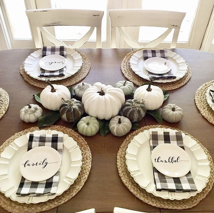 thanksgiving place setting black and white theme with checkered napkins, neutral colored pumpkins and white dishware