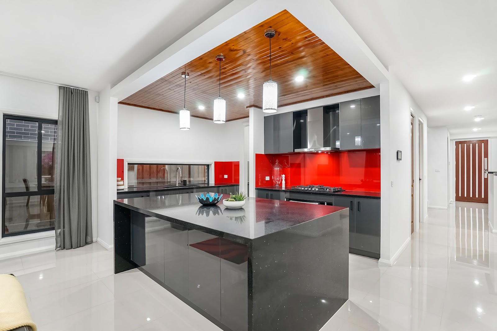 A sleek, modern kitchen with one red wall and granite countertop.