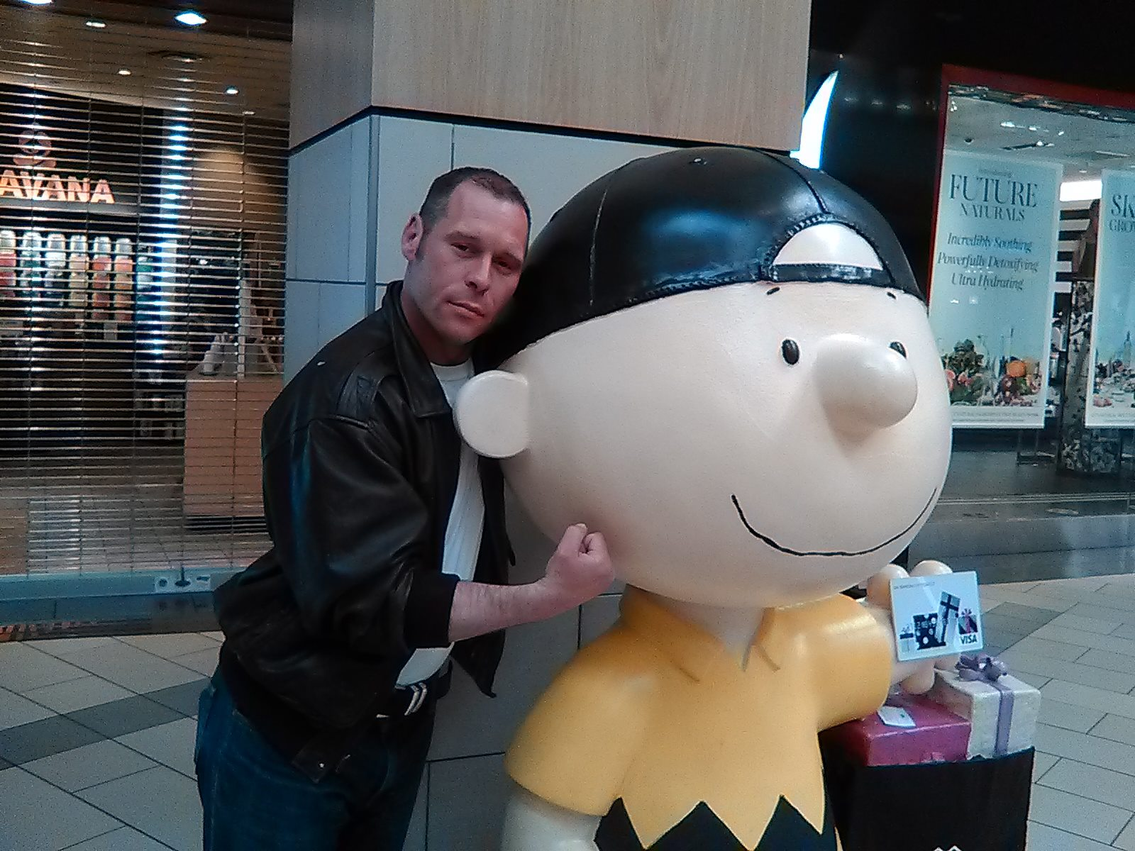 Barry, a white man in a leather jacket, stands next to a larger-than-life-sized statue of Charlie Brown in a backwards baseball cap. Barry is holding his fist against the statue's chin.