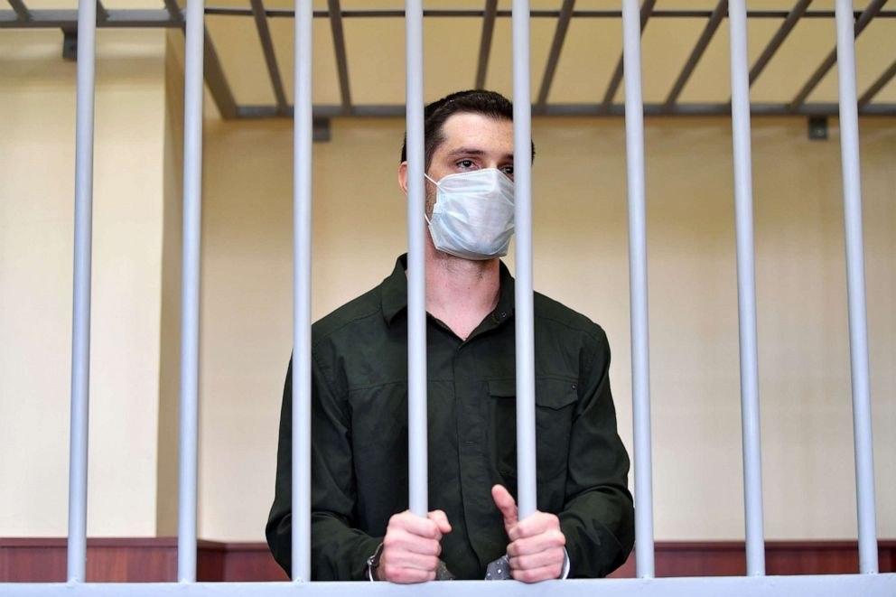 PHOTO: US ex-marine Trevor Reed, charged with attacking police, stands inside a defendants' cage during his verdict hearing at Golovinsky district court in Moscow, July 30, 2020.