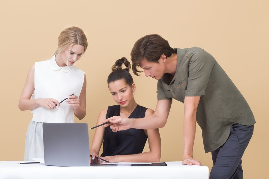 two women and a man looking at a computer screen and discussing work abroad job opportunities