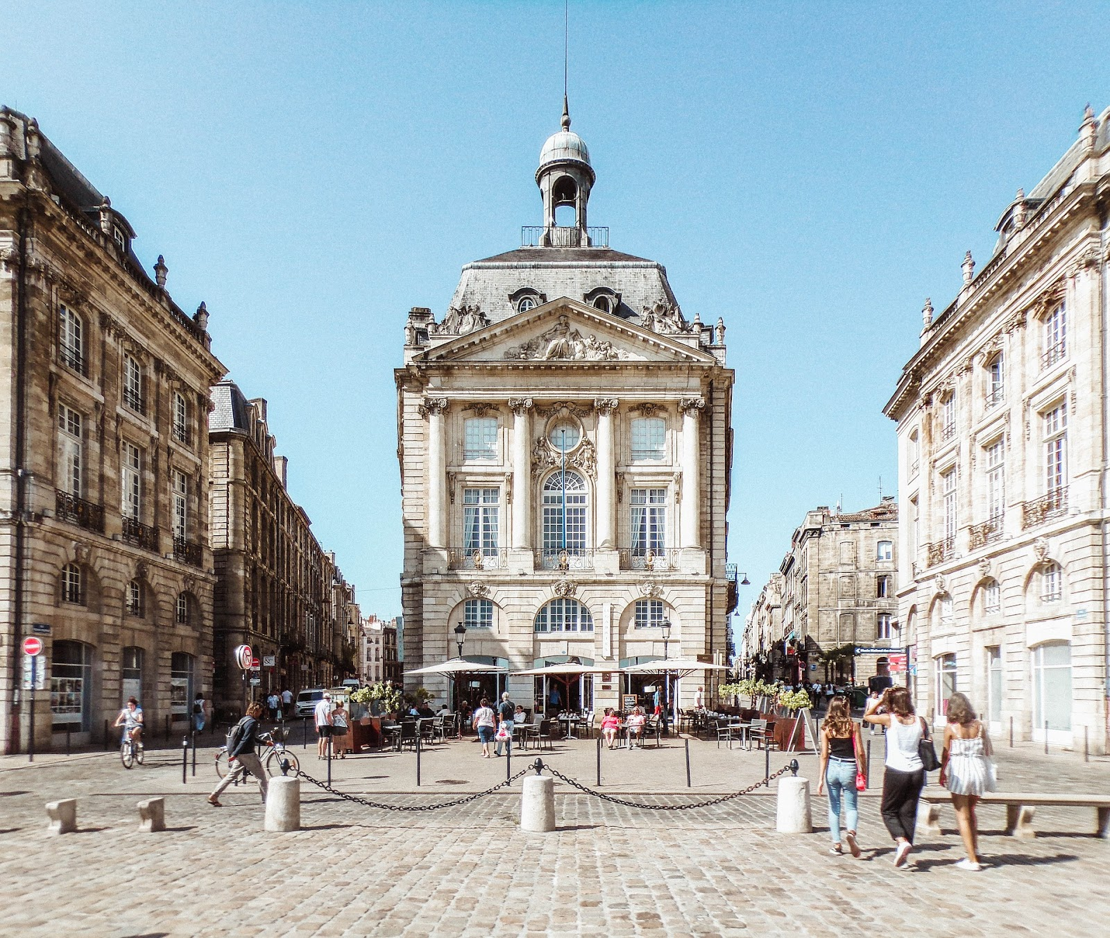 bordeaux france traditional white building with large windows, at a cobblestone square with tourists on a sunny day