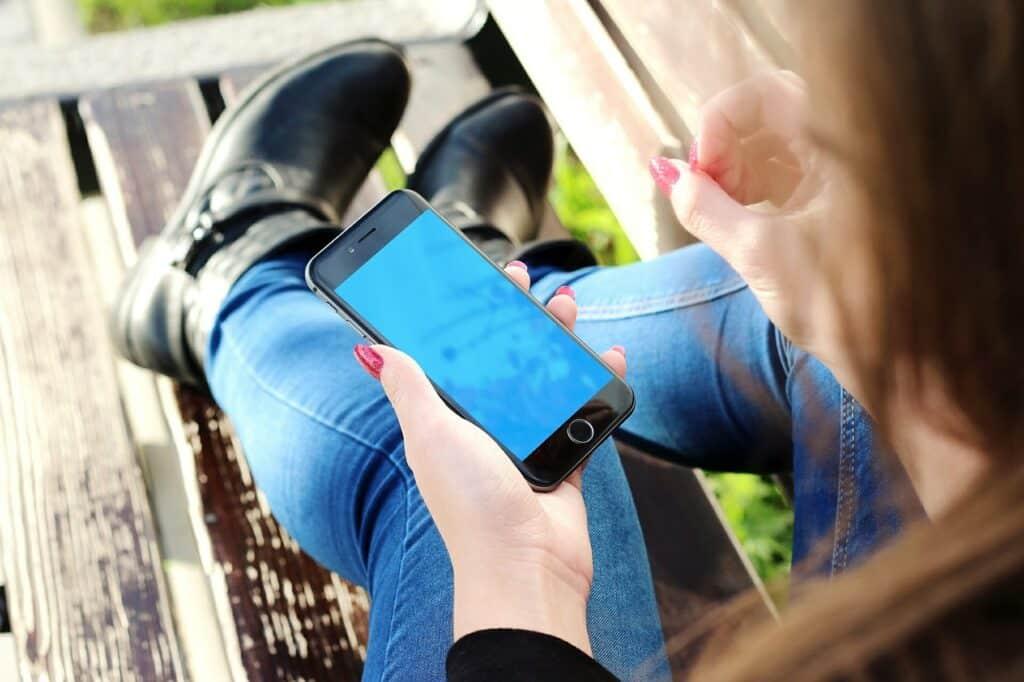 Mulher Com Unhas Pintadas De Rosa Segurando Um Iphone Preto