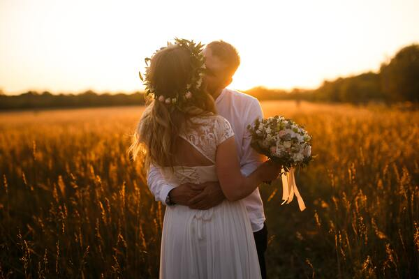 Noivo e noiva em um campo aberto se beijando.