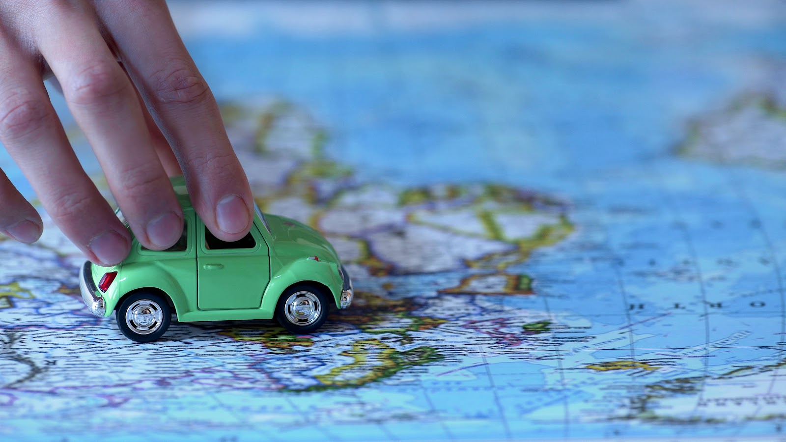 Someone using their hand to drive a small toy car over the top of a map of the world.