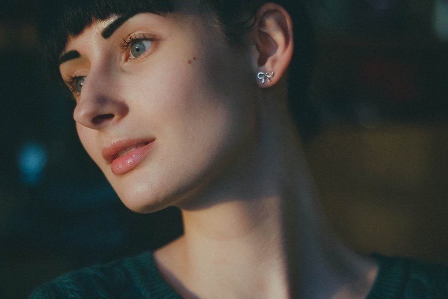 Woman Wearing Silver Earrings and Green Shirt