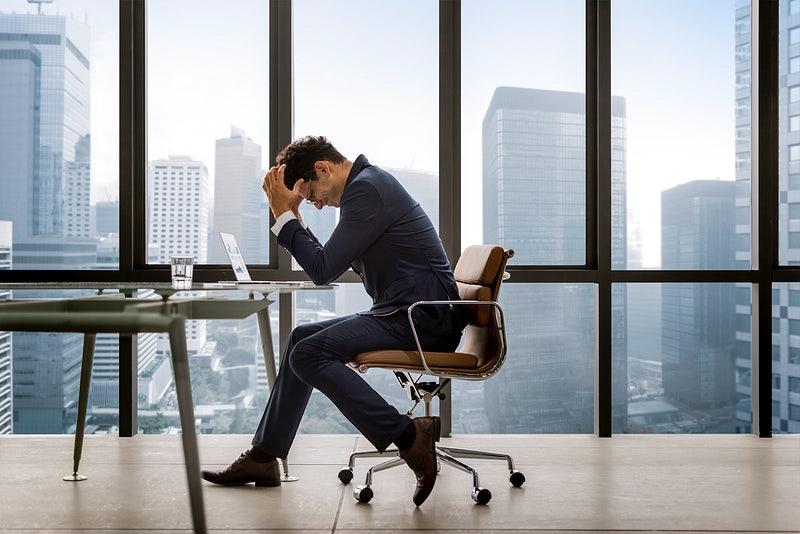 Um homem sentado fazendo gestos de desespero dentro de um escritório.