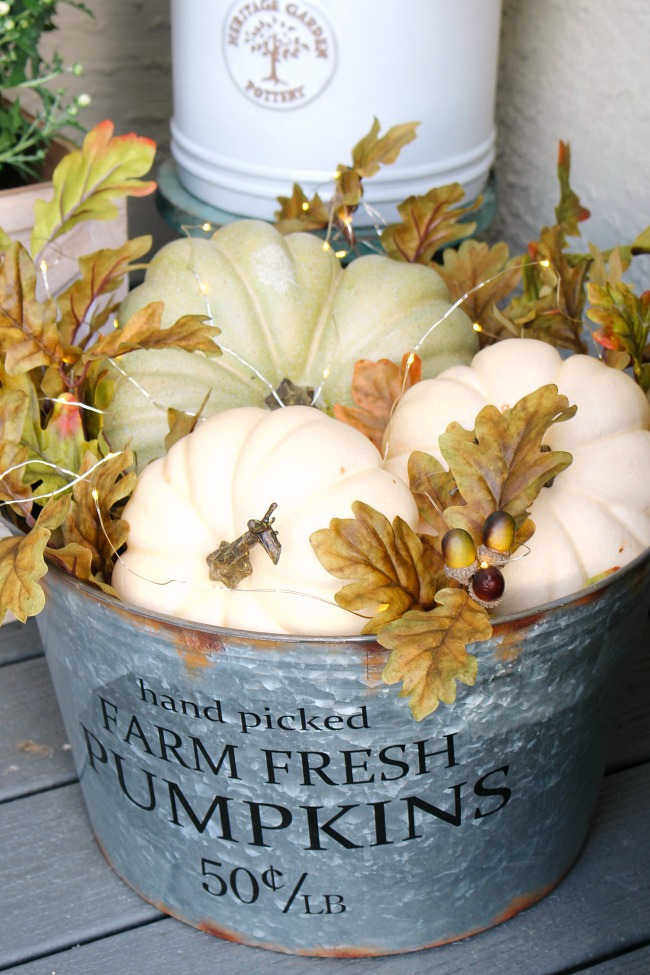 How To Use Pumpkins In Your Home to decorate. image shows vintage bucket full of white pumpkins with fall colored leaves and white lights.